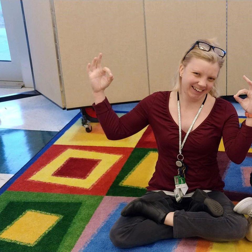 Sara Poole photo sitting on carpet in yoga pose