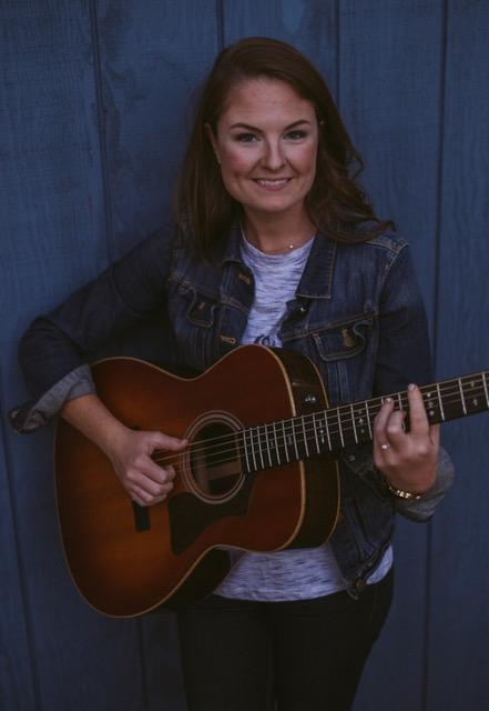 Maria Mulrine Brooke, music teacher is photographed holding a guitar
